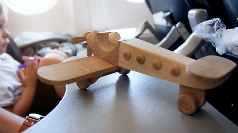 Closeup 4k video of toy wooden airplane against aircraft illuminator during Archivo