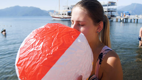 4k video of young woman blowing inflatable colroful beach ball at sea Footage