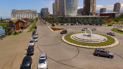 Automobiles moving down roundabout crossroads on Heroes Square in Batumi Georgia Live Action
