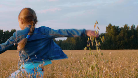 Happy teenager girl dancing at oat field. Cirl teenager walking on wheat field Live Action