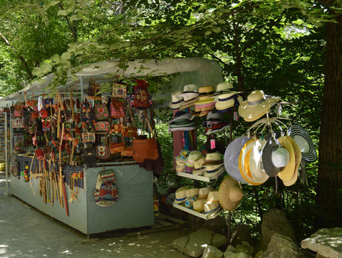 Outdoor souvenir kiosk in the Park with tourist goods hats, bags, backpacks and Photo
