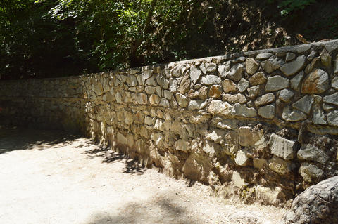 High stone fence along the pedestrian rural path in summer Sunny day Photo