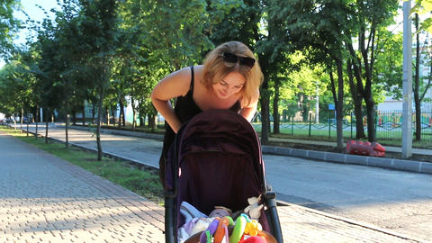 Mom lovingly looks at her daughter and shakes her in a stroller. Beautiful young ビデオ