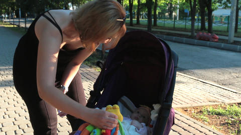 Mom plays with the baby lying in a pram on a walk Footage