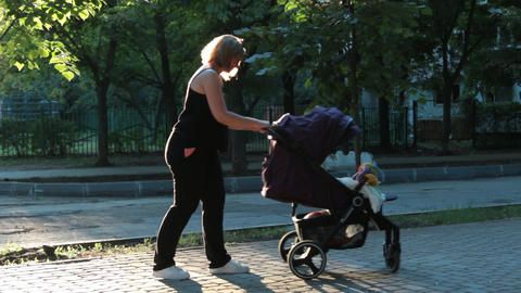 Mom with baby, lying in a stroller on an evening walk. Urban landscape Footage
