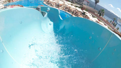 Slow motion POV video of young man riding down on water slide at aquapark Footage