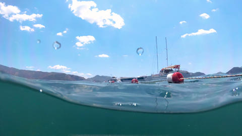 Slow motion underwater footage of moored yachts and life buoys in the sea Footage