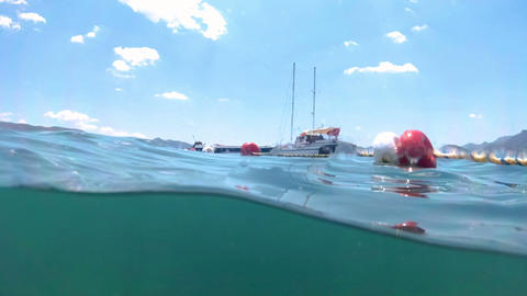 Slow motion underwater footage moored yachts in sea at bright sunny day ビデオ
