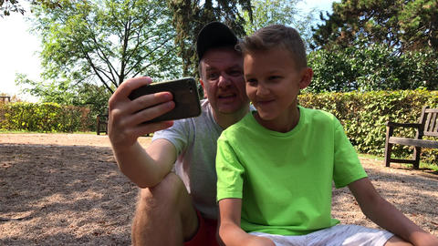 Parent and child take selfie in park Footage