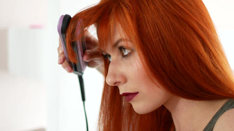 Red-haired woman balancing her hair with an iron before the mirror Footage