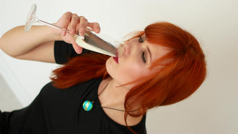 Close-up of smiling woman drinking a glass of champagne against white background Footage