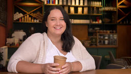 Fubsy caucasian girl looking at camera and smiling holding big cup of coffee Footage