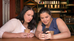 Two big caucasian women surprisingly watching at mobile phone indoor with two Footage