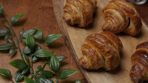 Fresh croissant a flaky, viennoiserie pastry on wooden board Footage