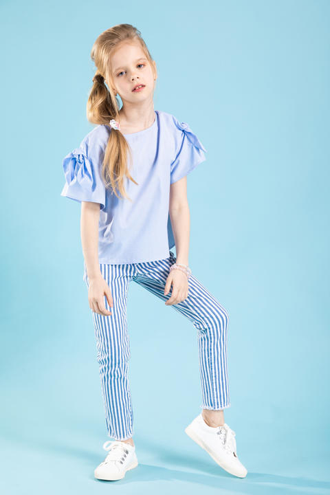 Full-length portrait of a beautiful girl in blue clothes on a blue background Fotografía