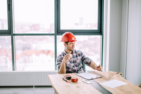handsome engineer is holding a cup of tea Photo