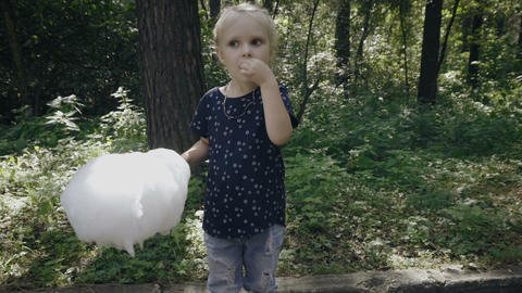 Little blonde girl is eating cotton candy Archivo