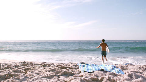 A man is running with his surfboard Footage