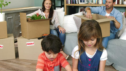 A family of four unpacking boxes Live Action