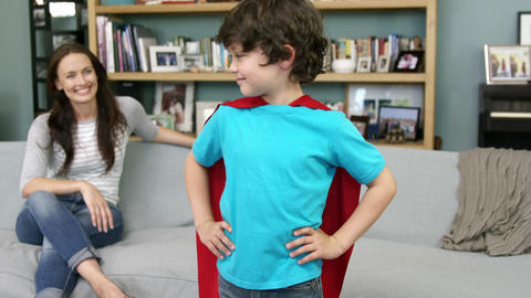 Little boy pretending to be superhero while his mother is sitting Footage