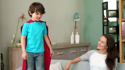 A little boy pretending to be superhero while his mother is watching him Footage