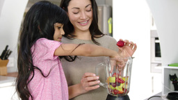 Mother and daughter cooking fruit in the kitchen Footage
