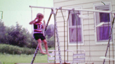 1968: Daredevil boy swinging on playground using hanging pull up bar Footage