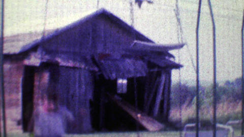1968: Boy swings hard in family playground with old barn in background Footage