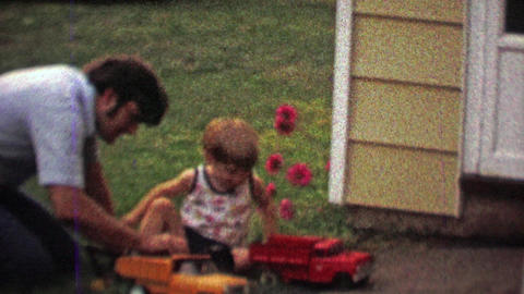1968: Dad and son playing toy model dump and fire trucks backyard Footage