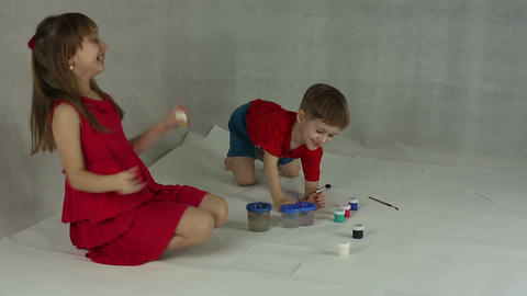Children draw on paper with brushes and gouache Footage