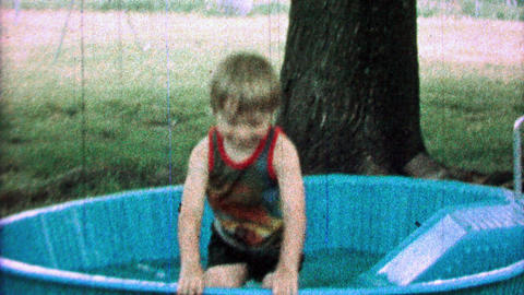 1968: Boy goes down kiddie slide into play swim pool with clothes on Footage
