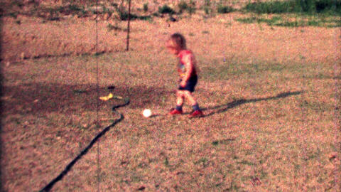 1968: Toddler boy practices baseball throw fielding grounders Footage