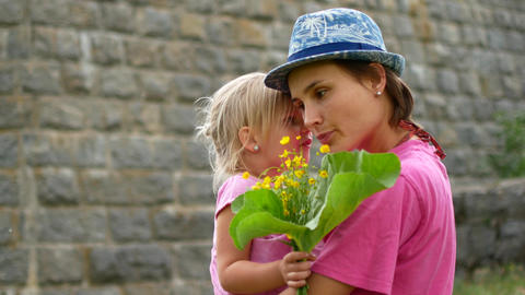 Beautiful Young Mother Embracing Her Cute Daughter with Yellow Bright Flowers on Footage