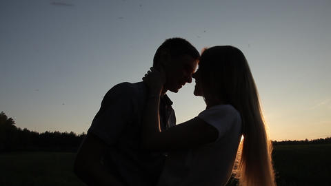 Guy girl kissing and hugging in the field at sunset Footage