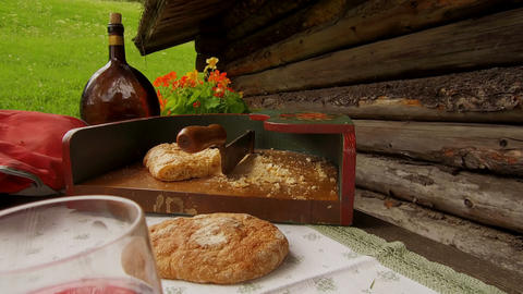 Close detail on a teenager dressed in typical Tyrolean dress, cut dry bread with Footage