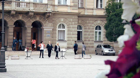 People Walk by the Old Building in the City Center Footage