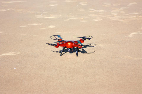 orange drone standing on the sand. Sunny day フォト