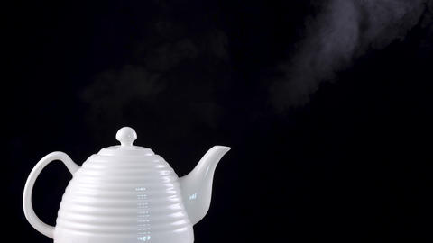 Tea pot on black background with boiling water Live Action