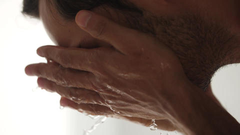 A man is washing his face with water Slow motion video GIF