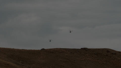 Two helicopters fly over the hills to the horizon Slow motion Footage
