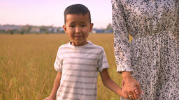Lovely asian boy go step by step after his tender mother while holding her hand Footage