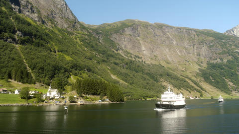 Ship Sailing past Small Village in Norway Fjords Live Action