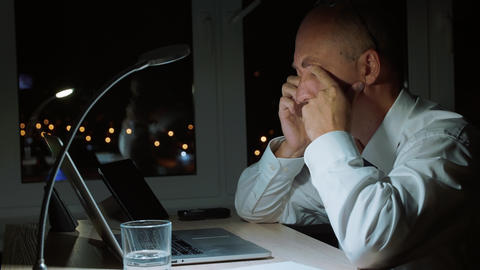 Executive businessman rubbing eyes while hard work by notebook in night office Footage