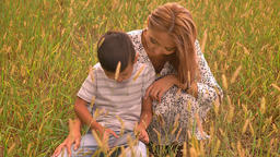Asian cute boy and his loving mother swiping table while sitting on grass Footage