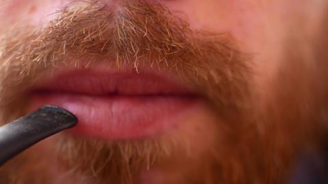 full face young man smoking outdoor close-up. smoke fire light. . man's lips Footage
