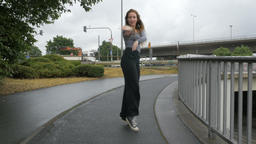 Young Woman Dancing on Rainy Sidewalk Archivo