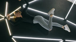 Female Dancer Lying Down and Stretching Legs on Dance Floor Footage