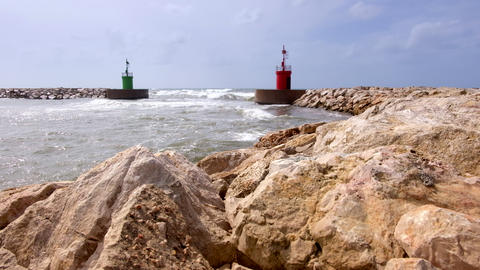 Sea current hitting on green and red lighthouse towers of a port entrance ビデオ