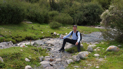 Man drinking water from bottle on shore rapid river while summer trekking Archivo