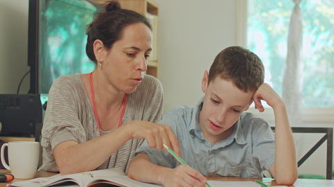 Mother helping her son to do his homework at home Live Action